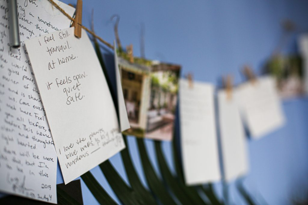 "Handwritten notes hanging on twine with clothespins. The note in the foreground reads ""I feel still. Tranquil. At home. It feels open. Quiet. Safe."