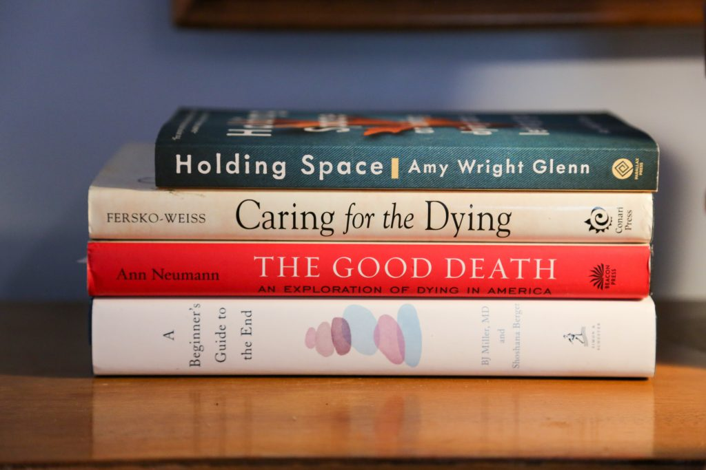 A stack of books about end-of-life care, including Holding Space by Amy Wright Glenn, Caring for the Dying by Ferko-Weiss, The Good Death by Ann Neumann and A Beginner's Guide to the End, by BJ Miller, MD.