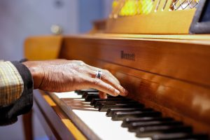 Close-up image of a hand hovering above the keys of a piano.