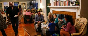 Friends and family of all ages enjoying a potluck dinner in the common space